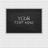 Blank chalkboard, blackboard hanging on the white brick wall with copy space Royalty Free Stock Images
