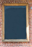 Blank chalkboard on brick wall Stock Photography
