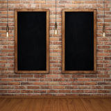 Blank chalkboard on brick wall with glowing light bulbs. 3D rendering Stock Photos