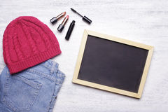 Blank chalkboard with copyspce and women's essentials on white w Stock Photos