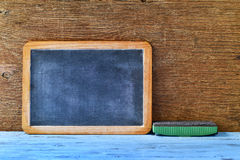 Blank chalkboard and an eraser on a blue wooden table Stock Photography