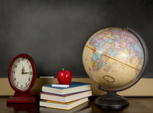 Blank Chalkboard with globe, books and clock. A desk with a globe, books, able and clock with a blank chalkboard in the background Royalty Free Stock Image