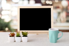 Blank chalkboard and green coffee cup standing over blur restaur Stock Photography