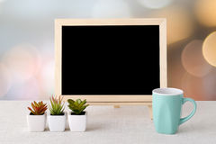 Blank chalkboard and green coffee cup standing on sack tableclot Stock Image