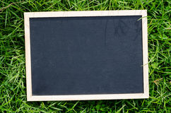 Blank chalkboard in green grass Royalty Free Stock Images