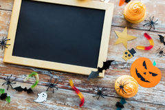 Blank chalkboard and halloween party decorations. Holidays, school and party concept - halloween decorations and treats with blank chalkboard on wooden boards Royalty Free Stock Photo