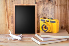 Blank chalkboard with plane camera and notebook stock image