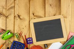 Blank chalkboard with school supplies border on wood Stock Photos