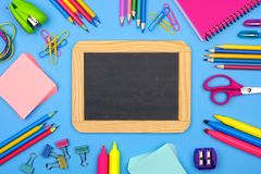 Blank chalkboard with school supplies frame over a blue background stock images