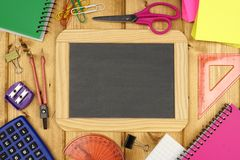 Blank chalkboard with school supplies on wood Stock Image