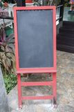 Blank chalkboard sign menu board with red frame and red stand in front of restaurant Royalty Free Stock Photography