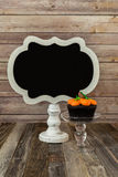 Blank chalkboard sign and pumpkin muffin on glass stand Royalty Free Stock Images