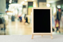 Blank chalkboard standing on sack tablecloth over blur store wit Royalty Free Stock Photo