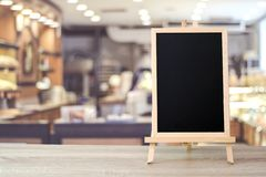 Blank chalkboard standing on table over blur cafe with bokeh bac royalty free stock images