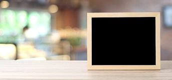 Blank chalkboard standing on table over blur store with bokeh ba Royalty Free Stock Image