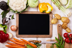 Blank chalkboard surrounded by fresh vegetables Royalty Free Stock Photo