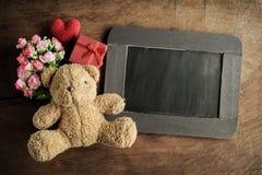 Blank chalkboard with teddy bear and flowers Stock Photos