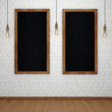 Blank chalkboard on white brick wall with glowing light bulbs royalty free illustration