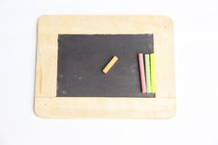Blank chalkboard with a wooden frame. And colorful of chalks Royalty Free Stock Images