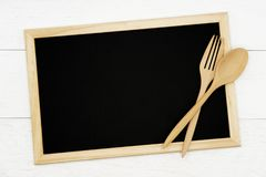 Blank chalkboard with wooden spoon and fork on white wood plank background. royalty free stock photography