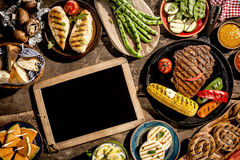 Blank Chalkboard on Wooden Table with Grilled Meal Royalty Free Stock Photo
