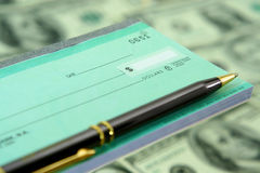 Blank Check and Pen. Blank check with pen [floating] over paper money background Royalty Free Stock Photos