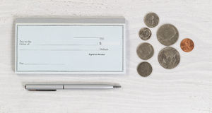 Blank checkbook with pen and coins on white desktop Stock Photos