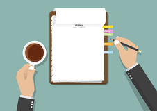 Blank checklist clipboard with businessman's hand holding black pencil and a cup of coffee. Royalty Free Stock Photo