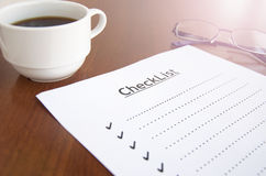 Blank checklist. On wooden table With coffee and glasses Royalty Free Stock Photography