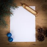 Blank Christmas card ,pine cones and pencil on wooden backgroun Royalty Free Stock Images