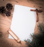 Blank Christmas card ,pine cones and pencil on wooden backgroun Stock Image