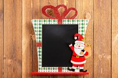 Blank Christmas decorated chalk board good for texts to be added. On wood background royalty free stock image