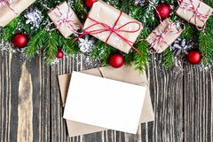Blank christmas greeting card and envelope with fir tree branches, gift boxes, decorations and pine cones Stock Image