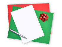 Blank Christmas Paper and Letter. A white, green and red blank pieces of paper are on a white isolated background, A pen is on top ready to write a letter. There Stock Photos