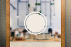Blank circular sign on glass door Royalty Free Stock Images