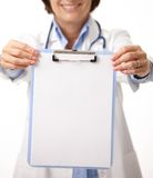 Blank clipboard held by smiling doctor. Stock Image