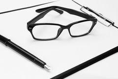 Blank clipboard with pen and eyeglasses Royalty Free Stock Photo
