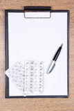 Blank clipboard, pen and pills on wooden table Stock Photos