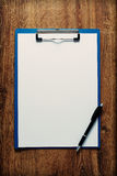Blank clipboard and pen on a wooden desk Royalty Free Stock Photos