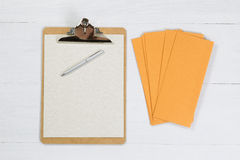 Blank clipboard with silver pen and envelopes on white desktop Royalty Free Stock Photography