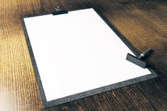 Blank clipboard with stamper. Closeup of blank clipboard and stamper on wooden surface. Mock up, 3D Rendering Royalty Free Stock Image