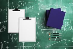 Blank clipboard and supplies. Top view and close up of blank clipboard, document folders and other supplies on chalkboard background. Mock up, 3D Rendering Stock Photo