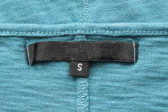 Blank clothes label. Blank black clothes label clousep on blue cloth royalty free stock image