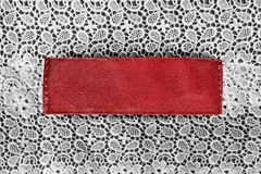 Blank clothes label. Blank red textile clothes label on white cotton lace as a background stock photo