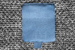 Blank clothes label. Blank blue textile clothes label on grey knitted background royalty free stock photos