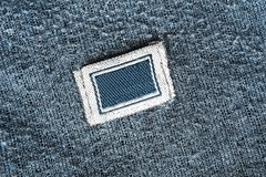 Blank clothes label. Blank textile clothes label on blue knitted background closeup royalty free stock images