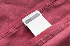 Blank clothes label. Blank white clothes label on red cotton as a background Stock Photo
