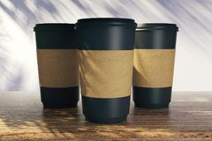Blank coffee cups with shadows. Blank coffee cups with palm tree shadows. Vacation and cafe ad concept. Mock up, 3D Rendering Stock Photos