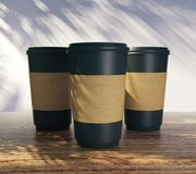 Blank coffee cups with three shadows. Blank take away coffee cups with palm tree shadow. Advertisement, shop and vacation concept. Mock up, 3D Rendering Stock Photos