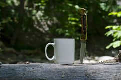 A blank coffee mug and a buck knife. A view of the blank white coffee mug and a buck folding knife stuck in a log in the woodland area of the forest in the stock image